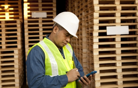 messaging: worker using smartphone in warehouse pallet Stock Photo