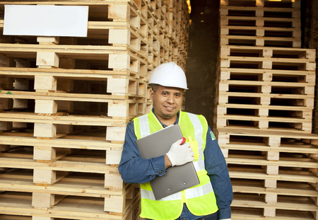 Senior worker standing relaxed in warehouse pallet photo