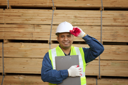 Senior worker standing beside stacked wood photo