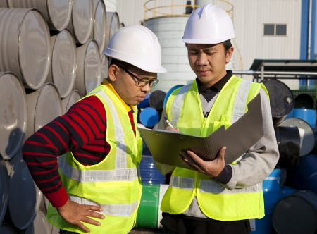 Two workers discussing about work with notepad document