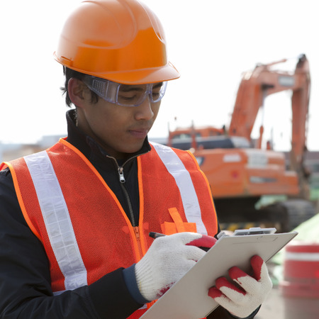 heavy equipment operator: road construction worker checking a document on the excavator