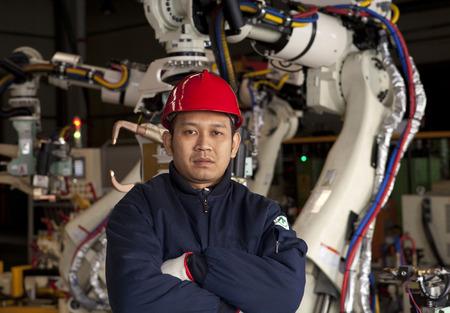 Industry engineer standing beside robot machine