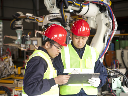 industrial worker: Two manufacture worker discussing in factory