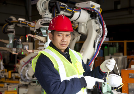 Factory worker pointing safety mask with robot machine on the background photo