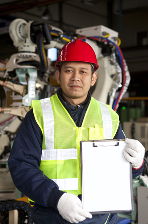 Engineer  holding a notepad with robot machine on the bacground photo
