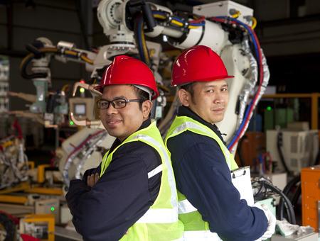 Two engineer standing beside robot machine Reklamní fotografie