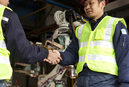 Two engineer shaking their hands at a manufacturing area Imagens