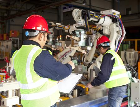robot: Trabajadores de la f�brica del equipo en el trabajo Foto de archivo