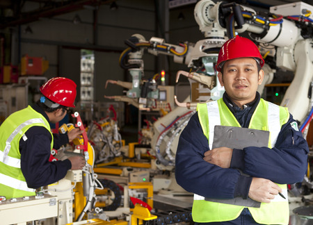 laborers: Factory worker standing with partner on the background Stock Photo