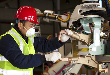 Industrial machine operator checking on robot machine