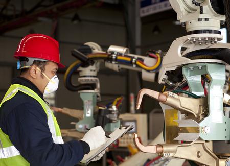 mecanica industrial: Comprobar T�cnico m�quina robot Foto de archivo