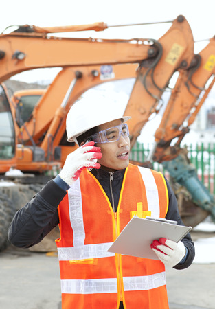 Construction worker talking on the phone and holding clipboard photo