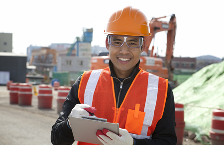 Smiling construction worker standing on construction   site photo