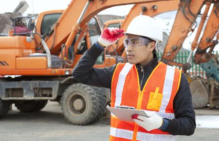 Construction worker inspecting on building new site Standard-Bild