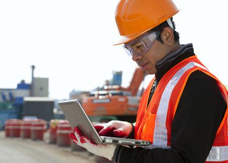 배경에 굴삭기와 함께 노트북을 사용하는 건설 노동자 스톡 콘텐츠