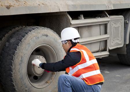 safety check: Trabajador de la construcci�n comprobar cami�n de neum�ticos