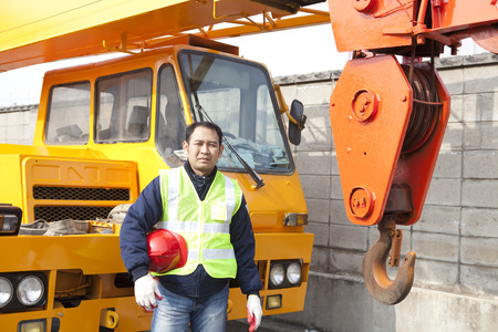 Driver crane truck posing next to the huge mobile crane with holding safety helmet