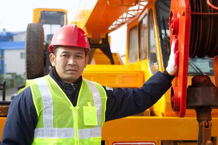 Construction worker standing on crane truck