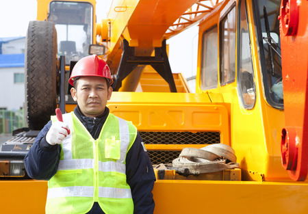 Construction worker giving thumb up with heavy equipment  Reklamní fotografie