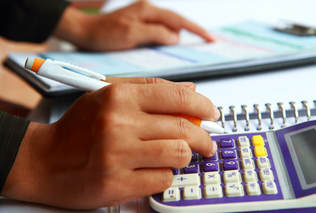 Close-up photo of business woman hand accounting financial report. Female hand with pen and calculator analyzing financial data photo