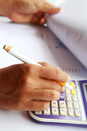 Close-up photo of business woman hand accounting financial report. Female hand with pen and calculator analyzing financial data Stock Photo - 26276223