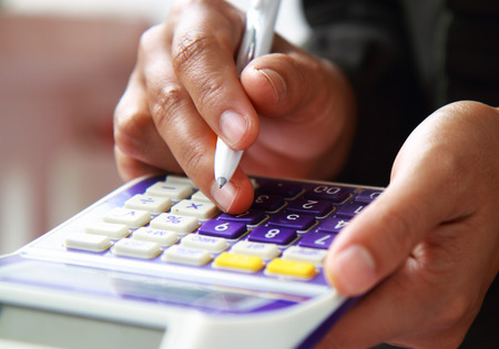 Close-up photo of business woman hand accounting financial report. Female hand with pen and calculator analyzing financial data