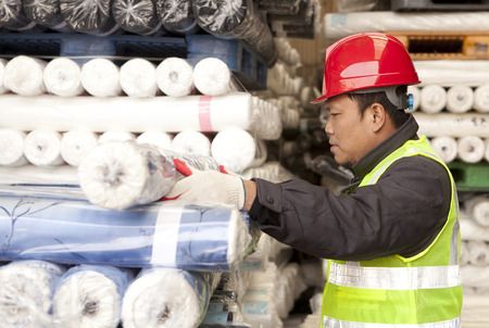 textile industry: Textile factory worker arranging fabric in werehouse Stock Photo