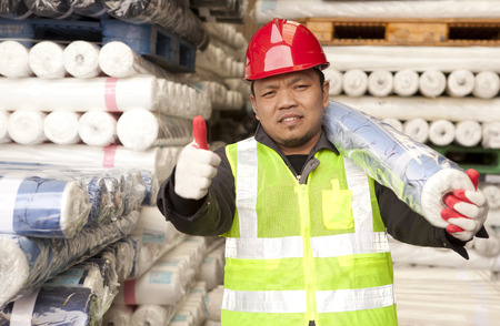 Textile factory worker carrying raw material fabric on his shoulder with giving thumb up Reklamní fotografie