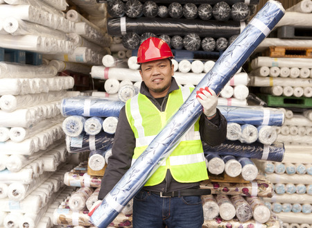 Textile factory worker carrying raw material fabric
