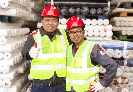 Two textile factory workers standing in werehouse raw material fabrics with giving thumb up Reklamní fotografie