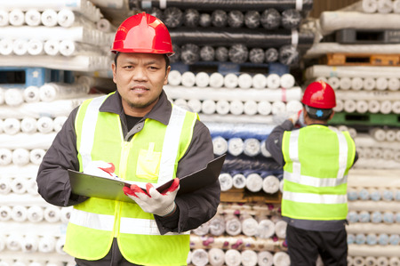 Portrait textile factory worker holding notepad with partner working on the background