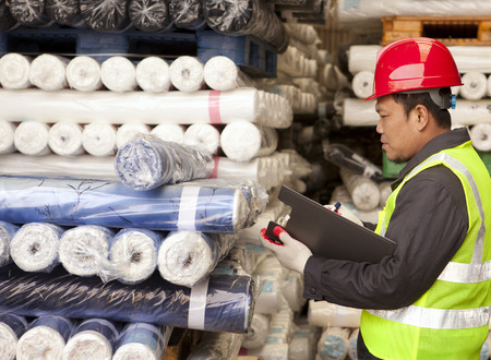 Textile factory foreman auditing raw material fabrics in warehouse Фото со стока