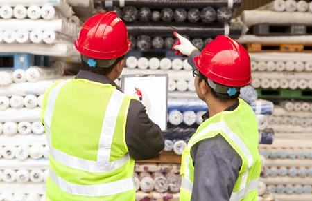 Twee arbeiders fabriek textiel inspecteren en controleren van grondstoffen stoffen in magazijn Stockfoto