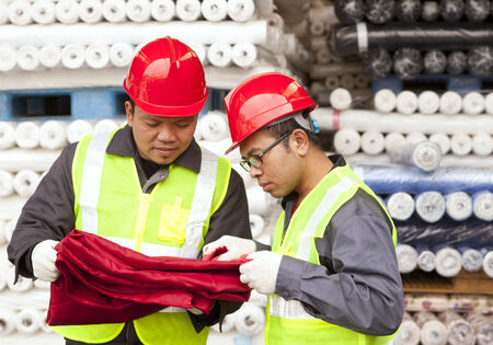 Two textile factory workers checking raw material fabric colour red in warehouse