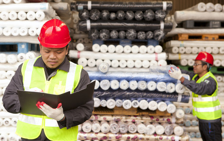 Textile factory worker writing on notepad with partner arranging raw fabrics on background photo