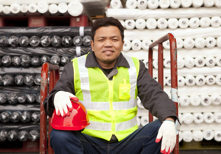 Textile factory worker sitting beside  raw material fabrics stacked photo