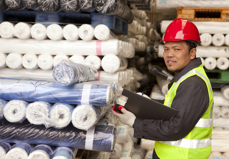 Textile factory foreman checking raw material fabrics in warehouse