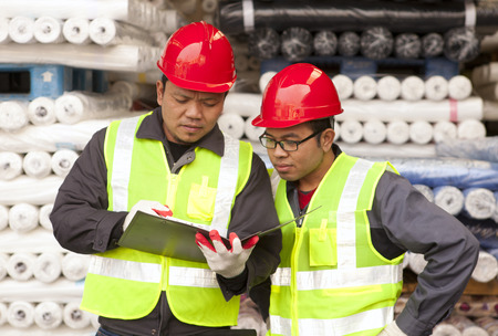 Textile factory workers discussing with stacked fabric on background