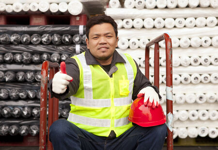 Textile factory worker sitting under raw material fabric with giving thumb up