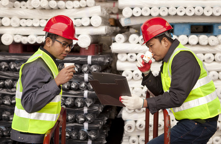 Textile factory workers discussing in warehouse fabric with drinking coffee photo