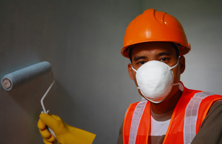 Painter worker wearing safety mask or safety work on job, painting of building house or apartment wall with roll Stock Photo - 27581351