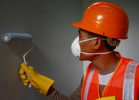 Painter worker wearing safety mask or safety work on job, painting of building house or apartment wall with roll Stock Photo - 27581352