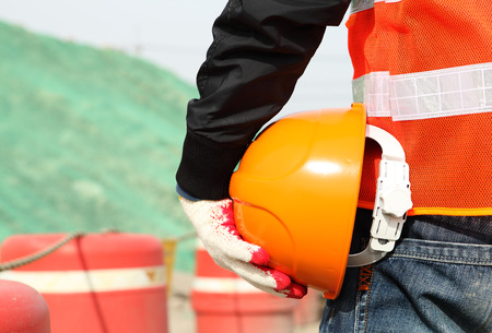 safety vest: Industrial construction safety work concept of man worker holding hardhat on location site