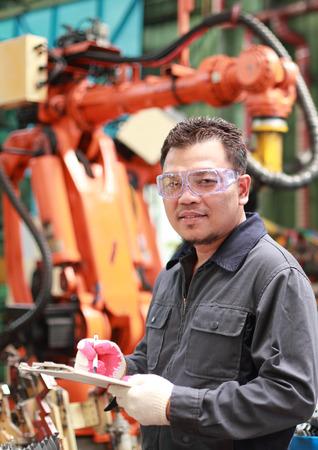 Factory engineer standing front arm robot machine