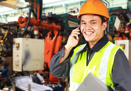 Factory engineer standing beside robot machine doing conversation on the phone