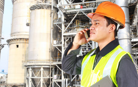 Industrial engineer standing in front of a large oil refinery conversation via phone