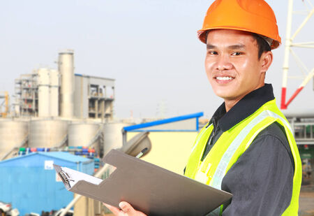 Chemical industrial  engineer wearing safety work with oil refinery in the background