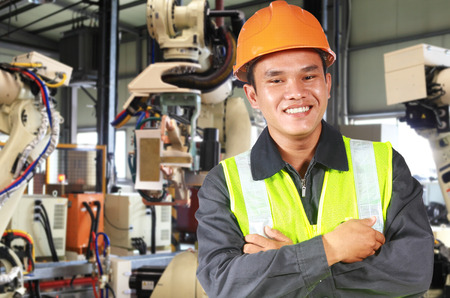 Man factory engineer or worker with robot machine inside modern industrial manufacturing, automobile industry photo