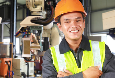 Man factory engineer or worker with robot machine inside modern industrial manufacturing, automobile industry