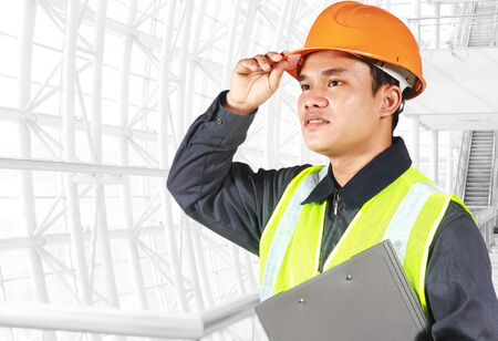 Portrait of an engineer looking at something, standing inside construction site photo